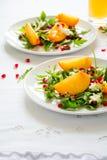 与柿子、芝麻菜、乳酪和石榴种子的新鲜的秋天沙拉在白色桌布 库存图片
