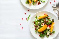 与柿子、芝麻菜、乳酪和石榴种子的新鲜的秋天沙拉在白色桌布 图库摄影