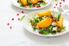 与柿子、芝麻菜、乳酪和石榴种子的新鲜的秋天沙拉在白色桌布 免版税图库摄影