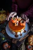 与柿子的秋天蛋糕和焦糖用一个南瓜和一个女孩伯根地礼服的在黑背景,大气黑暗的食物 免版税库存照片