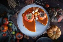 与柿子的秋天蛋糕和焦糖用一个南瓜和一个女孩伯根地礼服的在黑背景,大气黑暗的食物 库存图片