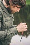 年轻与标尺的人渔夫有胡子的渔 免版税库存照片