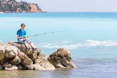 与标尺的白种人十几岁的男孩渔在海和海滩附近 库存图片