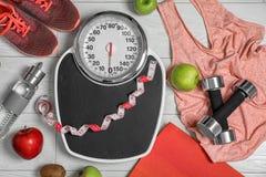 与标度、健康食品和运动器材的平的被放置的构成在木背景 库存照片