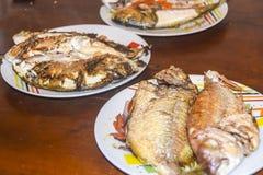 与标度的新鲜的油煎的被烘烤的在板材的鱼和柠檬 图库摄影