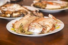 与标度的新鲜的油煎的被烘烤的在板材的鱼和柠檬 库存图片
