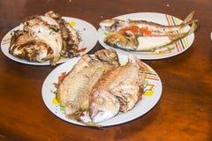 与标度的新鲜的油煎的被烘烤的在板材的鱼和柠檬 免版税图库摄影
