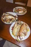 与标度的新鲜的油煎的被烘烤的在板材的鱼和柠檬 免版税库存图片