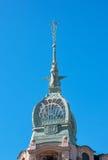 与标志众神使者的手杖的尖顶在大厦的屋顶 免版税库存照片
