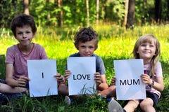 与标志的三个孩子我爱妈咪 免版税库存图片