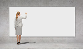 与标志的女实业家文字在白板 库存图片