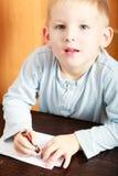 与标志的白肤金发的男孩儿童孩子图画在纸 胳膊详述她的家庭意图 免版税库存照片