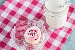 与标志的逗人喜爱的华伦泰杯形蛋糕 免版税库存图片
