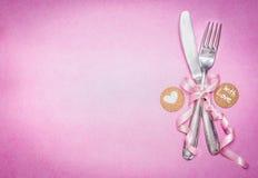 与标志装饰和消息的浪漫桌在桃红色背景,顶视图的餐位餐具您的和心脏 免版税库存照片