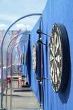 与标枪的掷镖的圆靶在街道上的蓝色墙壁上 免版税库存照片
