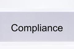 与标签服从的办公室文件夹在白色 免版税库存照片