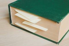 与标记页的大旧书由黄色稠粘的笔记 库存照片