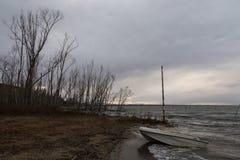 与树、多暴风雨的天气、云彩、水波和一条小的小船的湖岸 库存照片