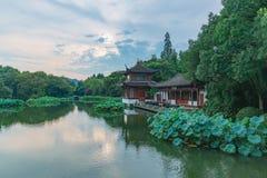 与树和中国房子的风景和反射在西湖,杭州,中国附近的水中 免版税库存图片