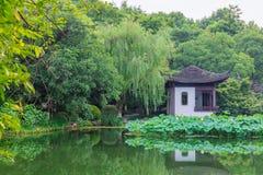 与树和中国房子的风景和反射在西湖,杭州,中国附近的水中 库存照片