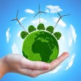 与树和风轮机的绿色行星 免版税库存照片