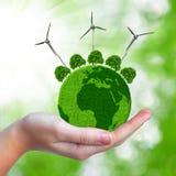 与树和风轮机的绿色行星 图库摄影