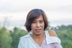 与树和Srinakarin水坝的画象亚洲妇女背景 免版税图库摄影