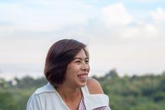 与树和Srinakarin水坝的画象亚洲妇女背景 免版税库存图片