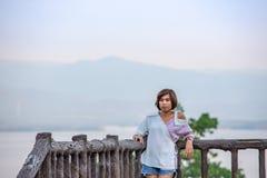 与树和Srinakarin水坝的画象亚洲妇女背景 库存图片
