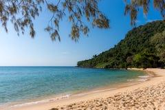 与树木丛生的陆岬的白色沙滩海湾在距离 库存照片