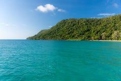 与树木丛生的陆岬的白色沙滩海湾 图库摄影