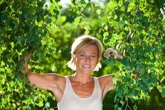 与树枝的逗人喜爱的妇女画象 免版税库存图片