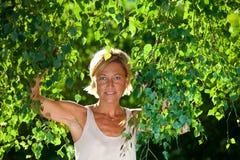 与树枝的逗人喜爱的妇女画象 免版税库存照片