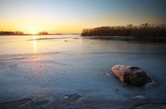 与树桩的美好的冬天风景在冰和日落 免版税图库摄影