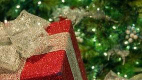 与树特写镜头的红色和金圣诞礼物 图库摄影