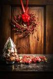 与树的圣诞卡从玻璃、曲奇饼和假日装饰在木背景与花圈和丝带 免版税库存图片