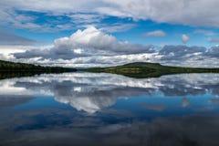 与树的小山和天空在湖反射了 库存照片