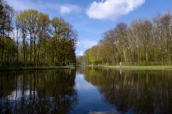 与树的美好的荷兰场面和他们的在运河的反射 免版税库存照片