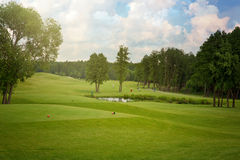 与树的高尔夫球领域在多云天空 免版税图库摄影