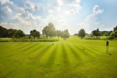 与树的高尔夫球领域在蓝天 免版税库存照片