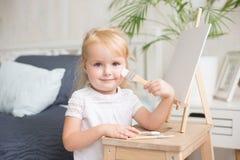 与树胶水彩画颜料和水彩油漆的愉快的儿童绘画在画架户内 图库摄影