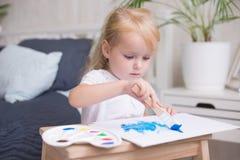 与树胶水彩画颜料和水彩油漆的愉快的儿童绘画在画架户内 免版税库存图片