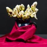 与栗子芽、花和小叶子的静物画构成在一个蓝色陶瓷罐有黑背景和紫色纺织品 免版税库存照片