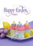 与样品的愉快的复活节桃红色,黄色和蓝色杯形蛋糕发短信 免版税图库摄影