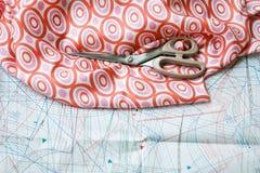 与样式的剪刀和丝绸材料在背景中 免版税库存照片