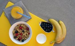 与格兰诺拉麦片、希腊酸奶、莓果、香蕉和新鲜的橙汁的健康早餐在灰色桌布的黄色切板 免版税库存图片