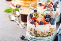 与格兰诺拉麦片、薄煎饼和莓果的早餐 免版税库存照片