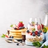 与格兰诺拉麦片、薄煎饼和莓果的早餐 免版税库存图片