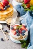 与格兰诺拉麦片、薄煎饼和莓果的早餐 库存图片