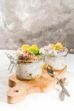 与格兰诺拉麦片,桔子,薄荷和可食的花的酸奶 免版税库存图片